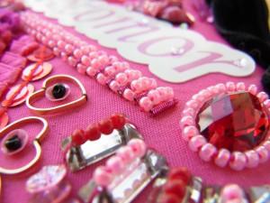 ピンクの生地にハート型のスパンコール、アクリルビーズ、丸小ビーズが刺してあります。