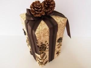 蓋に松ぼっくりが飾ってある縦長の箱です。