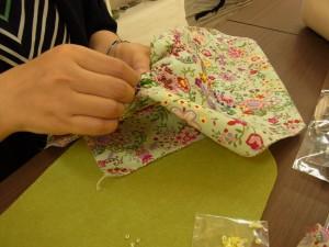 細かい花模様のビーズ刺繍を完成に向けて刺しています。