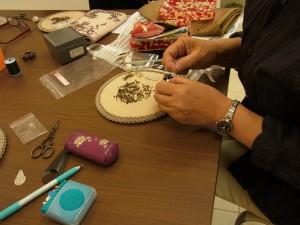 ブローチピンを先に縫いとめます。ビーズ、竹ビーズを使って刺していきます。