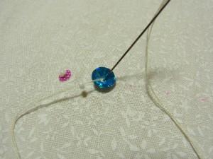 スパンコールとビーズの間に針を入れます。そのまま糸を抜きます。