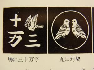 鳩が2羽向かい合っています。もう一方は鳩と三十万字の文字が描いてあります。