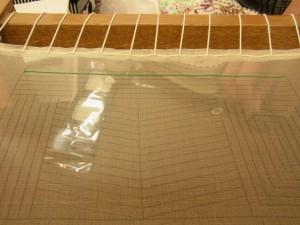 生地の両端を縫ってから木枠に張っていきます。ポリエステル糸で手前から向う側へ進んでいきます。