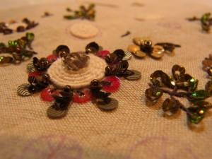 中央の立体的な花の周りに、紐を円形刺しています。