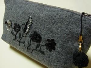 羊毛玉のアクセサリーが可愛いグレーのポーチです。