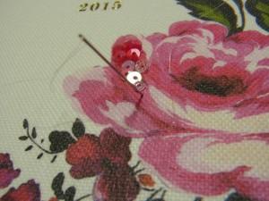 スパンコールを刺す位置に針で印をつけています。