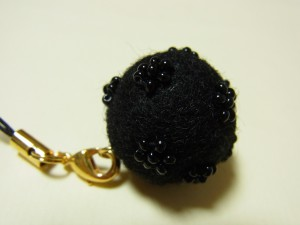 羊毛玉にビーズで刺した小花があります。
