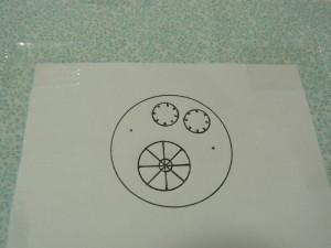 輪郭(29の円)に糸印をつけます。生地を表に返して、図案線の輪郭と糸印の輪郭を合わせてテープで固定します。