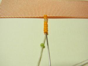 フリンジの長さ分のビーズを通します。最後に通したビーズひと粒を残し針を戻します