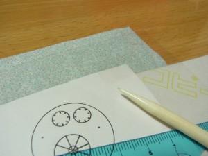 生地と図案紙の間にチャコペーパー(色が付いている方を生地に当てます)を入れます。その上にセロファン紙を被せテープで固定します。スケールと転写用のペンを使って生地に図案を写します。