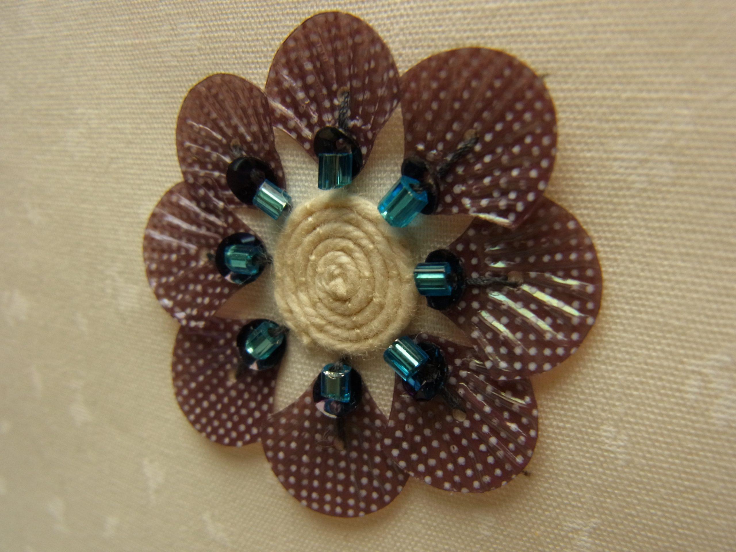 紐のグルグル巻きが中心にあります。花びらは、貝殻の形をしています。