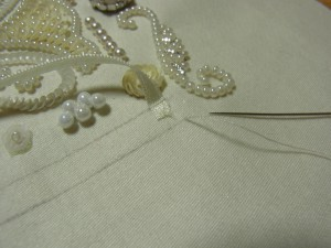リボンの先端を固定し、図案線の位置でリボンを糸で止めます。