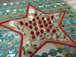 糸刺繍で星形をさしています。その周りは、ブルーのスパンコールで両止め刺しをしています。