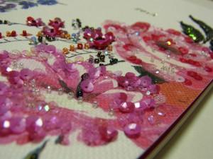 手帳の花柄にビーズ刺繍を施しています。