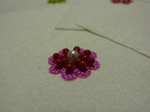 ピンクのドット模様スパンコール(フラット型)とビーズを、組み合わせて刺した円形の花です。