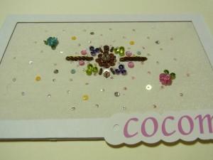 花をビーズ刺繍してあります。周りを固定しcococmorのタグが貼ってあります。