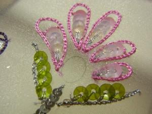 ピンクの糸で刺繍した中に、スパンコールを刺した花があります。