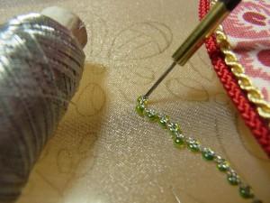 ビーズの両止めを、シルバーメタリック糸で刺していきます。