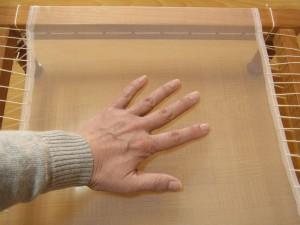 木枠に生地がピンと張れているか確認する為に、手のひらで軽く押します。
