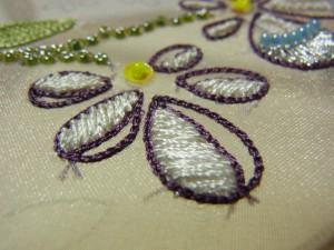 レーヨン糸2本どりで刺しています。白い花びらの縁を紫で囲って刺しています。