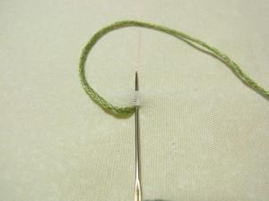 最初の糸を出した位置に再び針を入れ、チェーンステッチの長さの生地をすくいます。
