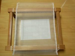 木枠に生地を乗せて、転写した図案が正確に中央へくるようにセットしたら、セロテープなどで固定します。