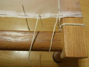 縦棒に針を下から上へ出して生地を張っています。
