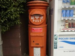 自販機の隣に佇むオレンジ色のレトロな郵便ポストです。