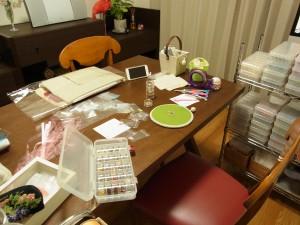 ハートのポプリを制作するので、その準備中です。テーブルの上は生地やビーズ、スパンコールが並んでいます。