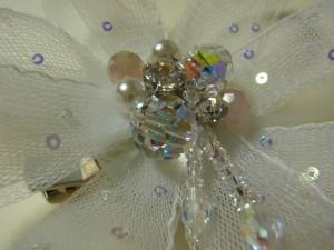白のコサージュの中心に、大きめのクリスタル、ストーン、パールを刺しています。フリンジも飾ってあります。