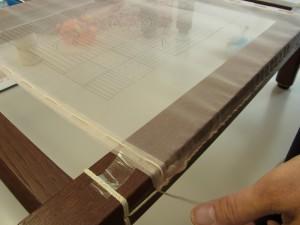 生地を木枠に張っています。図案の位置を決めたら、タコ糸で横棒の太い糸に縫い止めていきます。