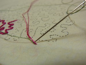 ピンクの糸を図案線上に置きます。ピンクの糸をまたぎ、グリーンの糸が出ている直ぐ側に針を落とします。
