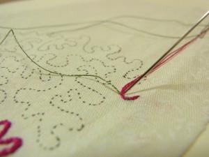 再びピンクの糸を図案線上に置き、グリーンの糸でコーチングします。