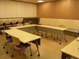 広いお部屋の中央にテーブルをコの字型に並べています。