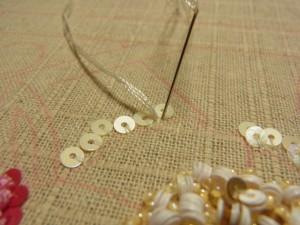 レーヨン糸は4本取りになります。スパンコールとスパンコールの間から針を出して、すぐ横隣に針を落とします。