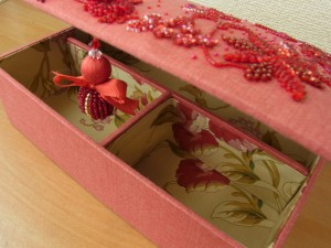箱の内側は仕切りが付いています。持ち手部分はビーズとリボンで作った、可愛い飾りが付いています。