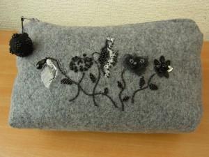 ポーチに5種類のお花が刺してあります。クリスタル、スパンコールが綺麗な円形に刺してあります。羊毛玉に刺してあるビーズも可愛く出来ています。