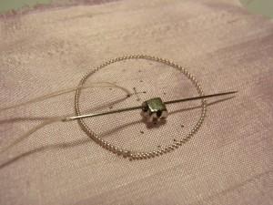 生地から針を出し、クリスタルの台座の穴に、横方向に針を通します。
