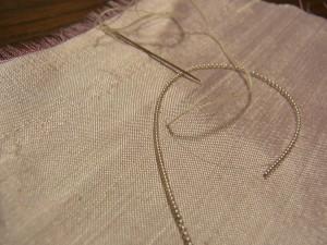 金属製のワイヤーを円形に刺しています。図案線から針を出します。