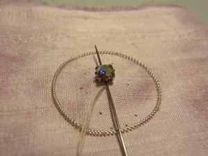 クリスタルの穴を、縦方向に針を通します。