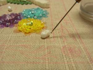 糸を引き出したら、前の糸の輪にくぐらせてビーズを固定します。