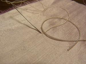 ワイヤーを図案線から少しずらします。ワイヤーをまたいで、糸が出ている直ぐ横に 針を落とします。