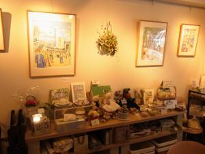壁に絵が飾ってあります。その下には、手作りの小物、ティディーベアー、カルトナージュ、などが飾ってあります。