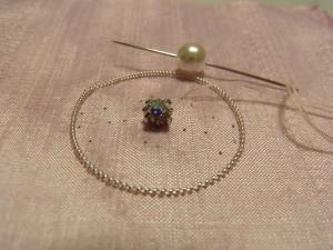 クリスタルの横から針を出し、パールを針に通します。