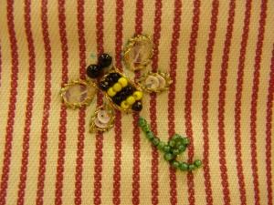 ポーチ裏面です。蜂の羽根の輪郭はメタル糸で、アウトラインステッチをしています。目、胴はビーズで刺しています。