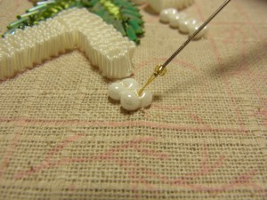 そら豆型ビーズの穴から糸を出しビーズを通します。