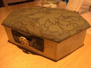 ジュエリーボックスです。台形の様な形で蓋が付いています。手前には可愛いリボンが飾ってあります。