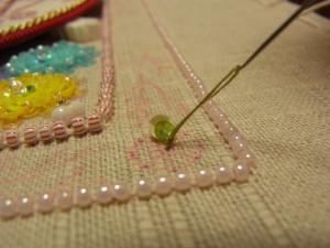 生地の上のスパンコールを固定する為に、糸を引き上げてきます。