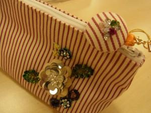 ポーチのファスナーの持ち手部分に、ビーズ刺繍をしたスチラップが付いています。