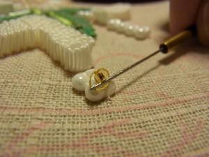 ビーズに輪をかけて、生地の下で糸を引っ張って絞めていきます。